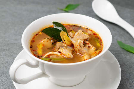 Cartilage pork stewed in spicy soup with Thai spices in white bowl on concrete table. Stock Photo