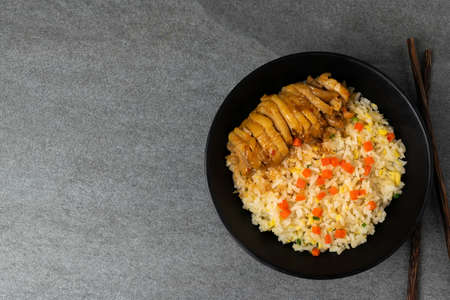 Fried rice with roast chicken and carrot in Korean style in black bowl on table. Reklamní fotografie