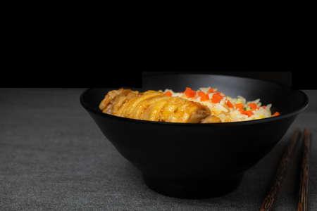 Riso fritto con pollo arrosto e carote in stile coreano in una ciotola nera sul tavolo.