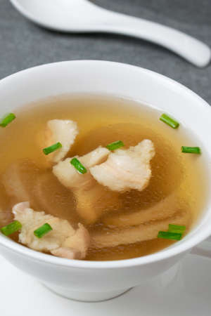 Radish soup with pork and scallion in white bowl on table.