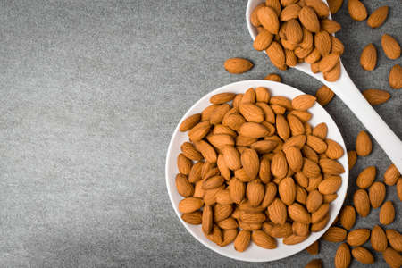 Almonds in white dish with spoon on table.