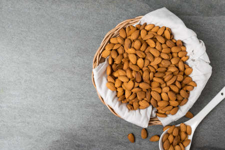 Almonds in basket and fabric with spoon on table.