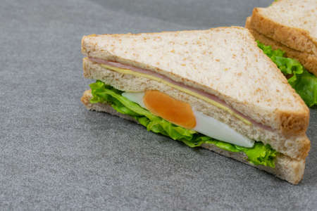 Homemade sandwich or toast wheat bread with lettuce and ham on the concrete table.