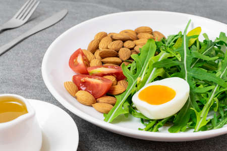 Arugula salad with almonds and tomato,boiled egg in white dish on tile table. Reklamní fotografie