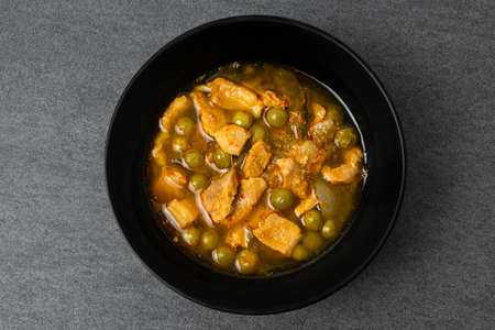 Belly pork or streaky pork in spicy curry soup with turkey berry in black bowl on tile table.