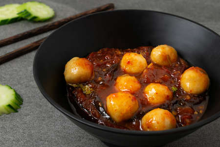 Meatballs with spicy sauce in black bowl on table.