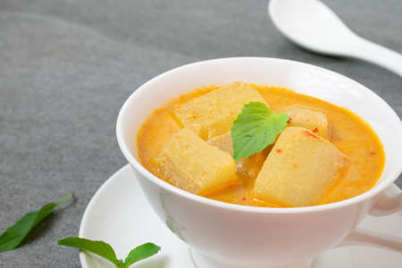 Coconut milk curry with winter melon in white bowl on table.