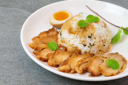 Grill chicken in soy sauce with rice and seaweed in Korean style in white dish on tile table. Reklamní fotografie