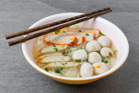 Rice stick noodles in broth with pork and meatballs in bowl on tile table. Reklamní fotografie