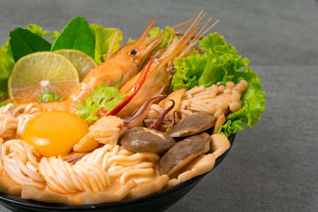 Noodle in spicy soup with shrimp and mushroom in black bowl on tile table.