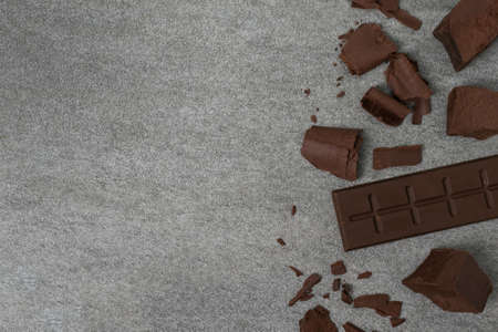 Broken chocolate with small piece on tile table.