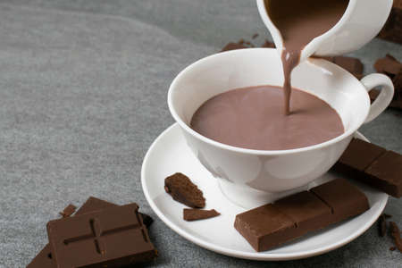 Broken chocolate with small piece and milk in glass on tile table. Reklamní fotografie