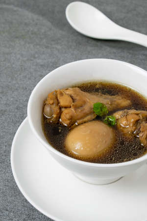 Hard-boiled eggs and chicken in sweet gravy soup in white bowl on tile table.
