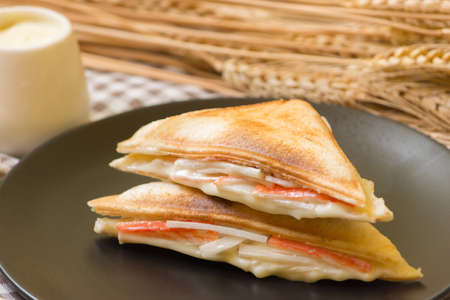 Sandwich stuffed with salad sauce and crab stick in black dish on wooden table.