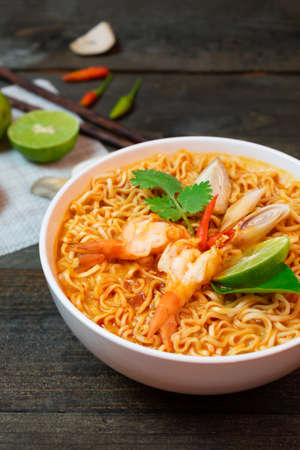 Noodle in spicy soup with shrimp and mushroom in white bowl on wooden table.