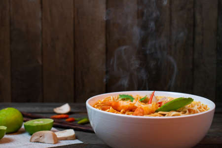 Noodle in spicy soup with shrimp and mushroom in white bowl on wooden table, Steam and Smoke. Stok Fotoğraf