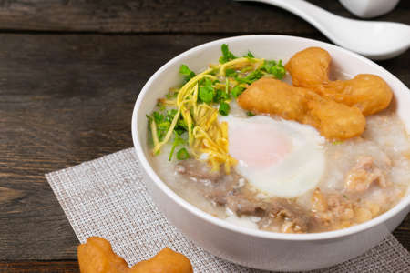 Rice gruel or Rice porridge with pork, onsen egg and deep fried dough stick in white bowl on wooden table.