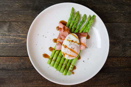 Asparagus in oyster sauce with onsen egg and bacon in white dish on wooden table background.