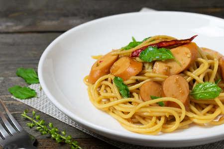Spaghetti mit Würstchen und gebratenem Basilikum im weißen Teller auf dem alten Holztisch.