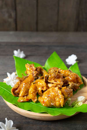 Fried dried squid on mango leaves in wooden dish.