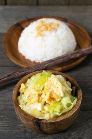 Fried cabbage and fried egg in oyster sauce, Rice in wooden dish.