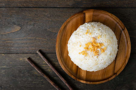 Rice with fried garlic in wooden dish on wooden table. Stock fotó