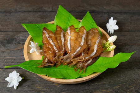 Fried dried fish on mango leaf in wooden dish on wooden table.