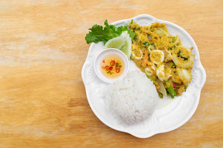 Stir fried squid in curry powder with rice and fish sauce mixed chili in white dish on wooden table. Stock fotó