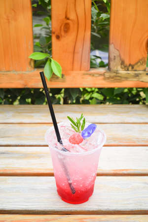 Strawberry Italian soda with butterfly pea flowers in plastic glass on wooden table.