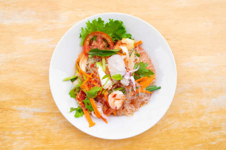 spicy vermicelli salad with seafood in white dish on wooden table.