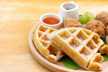 Waffles with fried chicken ball and grape in wooden dish on wooden table. Stock fotó