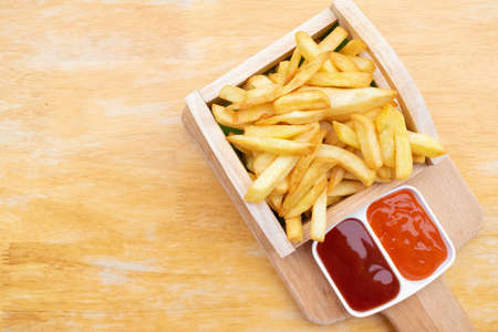 French fries in wooden tray with tomato and chili sauce on wooden table. Stock fotó