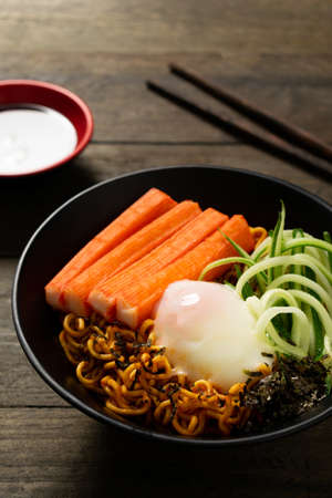Spicy instant noodle with crab stick and onsen egg and cucumber in black bowl on wooden table.