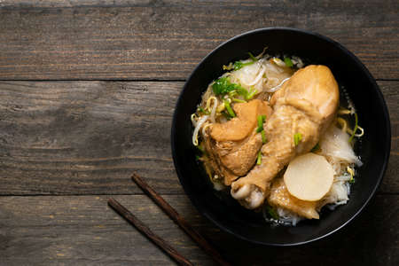 Rice noodle with chicken leg in black bowl on wooden table.