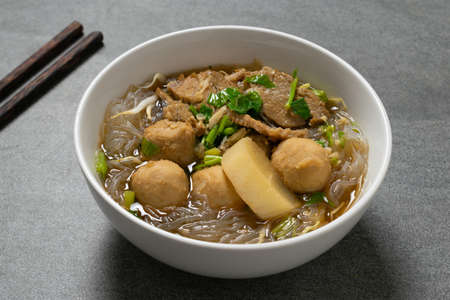 Vermicelli with beef in white bowl on concrete table.
