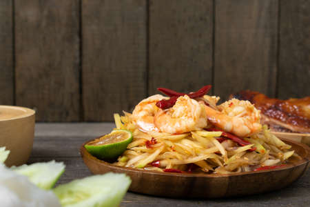 Papaya salad with pickled fish soup and shrimp in wooden table on wooden table.