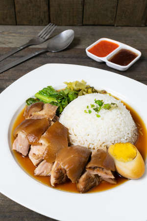 Pork leg rice with boiled egg in gravy and kale in white dish on wooden table.