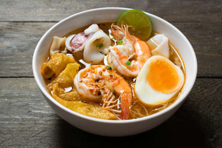 Spicy rice noodle with seafood and crispy wonton in white bowl on wooden table.