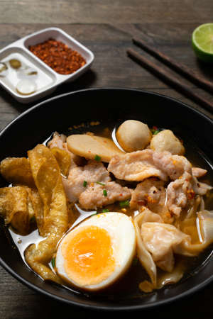 Spicy noodle with pork and crispy wonton in black bowl on wooden table. Stock fotó
