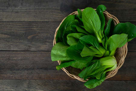 Fresh baby Bok choy in basket on wooden table. Stock fotó