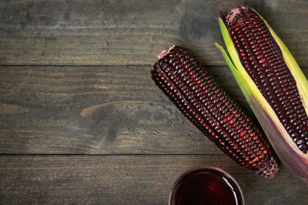 Fresh purple organic corn with juice on wooden table background.