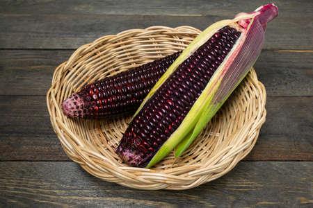 Fresh purple organic corn in basket on wooden table background. Stock fotó