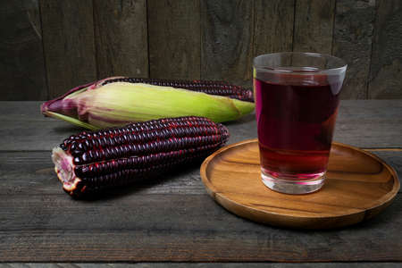 Purple corn juice in glass on wooden table background.