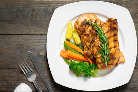 Steak chicken with rosemary and vegetables in white plate on wooden table.