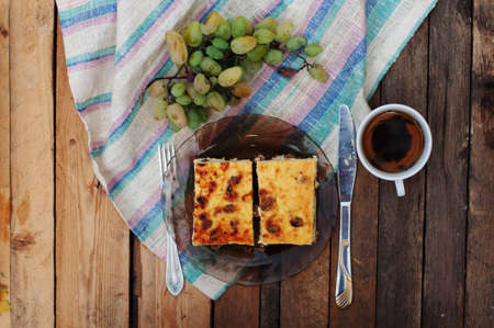 morning: cheese casserole in the dish with green grapes on a wooden background