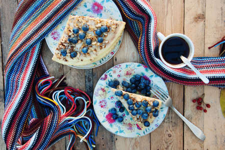 breakfast cup: Slice of delicious cake with fresh blueberry on wooden background.