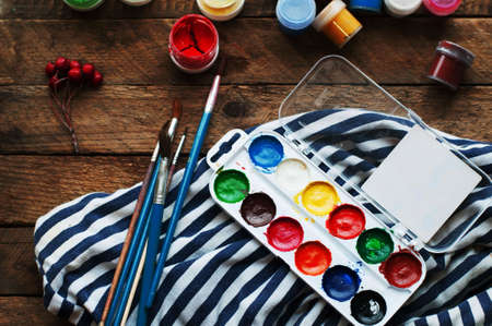 home decorating: Art of Painting. Paint buckets on wood background. Different paint colors painting on wooden background. Painting set: brushes, paints, crayons, chalk, watercolor, acrylic paint on a wooden background Stock Photo