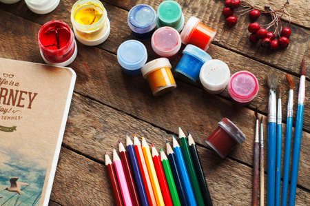 Art of Painting. Paint buckets on wood background. Different paint colors painting on wooden background. Painting set: brushes, paints, crayons, chalk, watercolor, acrylic paint on a wooden background