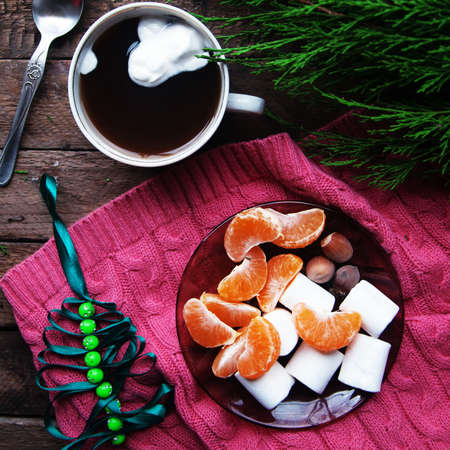 christmas spirit: Winter decoration. Composition on wood background. Hot tea, candles, cut grapefruit. Christmas. Christmas mood. Christmas spirit. Fir branches. Tangerine slices. Cones Stock Photo