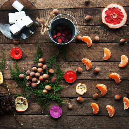 christmas toy: Winter decoration. Composition on wood background. Hot tea, candles, cut grapefruit. Christmas. Christmas mood. Christmas spirit. Fir branches. Tangerine slices. Cones Stock Photo